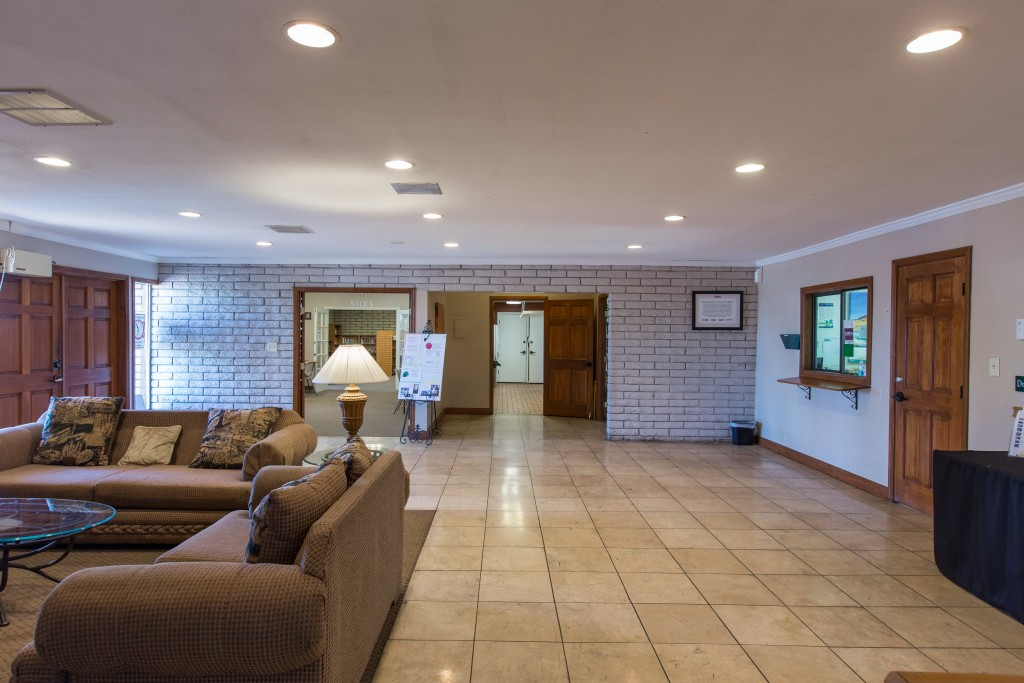 Lounge area with couches and table in the community center with the sales office included.