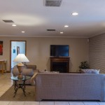 Lounge area in the community room with flat screen tv and 2 loveseats.