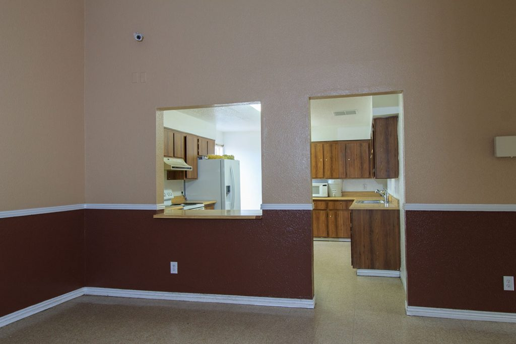 Community room has a kitchen with white fridge, microwave, sink oven