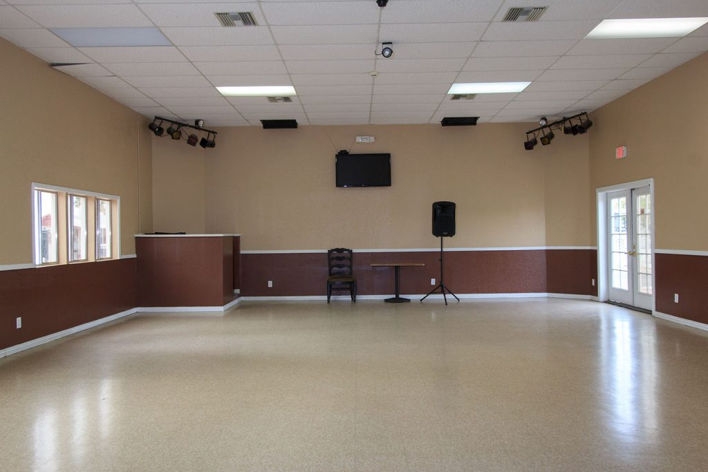 An open floor set up for dances with lights hung from ceiling, loud speaker and flat screen TV mounted to wall