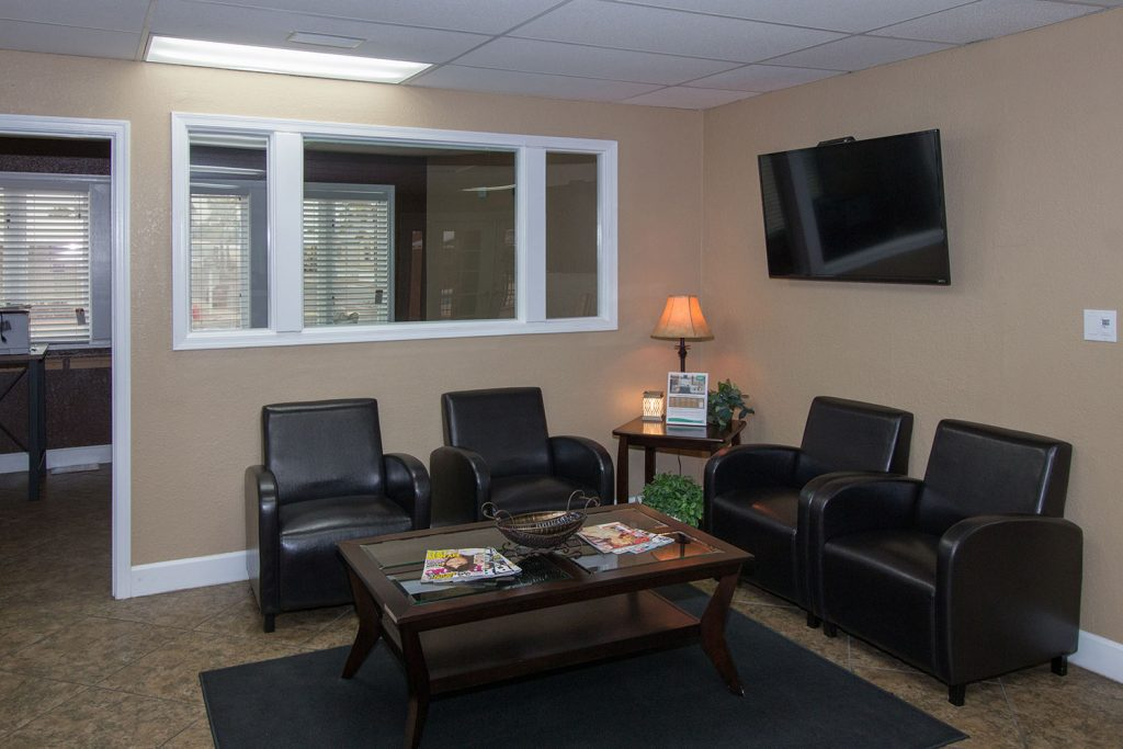 Lounge area in clubhouse with comfortable leather chairs and flat screen TV on wall