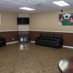 All tile floor in game room at Sierra Estates with flat screen on the wall. Leather couch and chairs and a folded up ping pong table