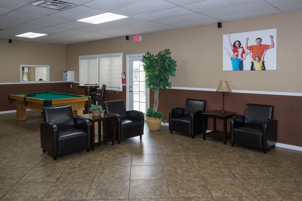 Tiled flooring in the billiards room with comfortable leather seating.