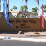 Silver Spur Village a 55+ community, has a sign at the entrance homes for sale flags.