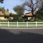 Beautiful view of the community center and pond, sitting behind a white picket fence and surrounded by well-maintained green grass and trees.