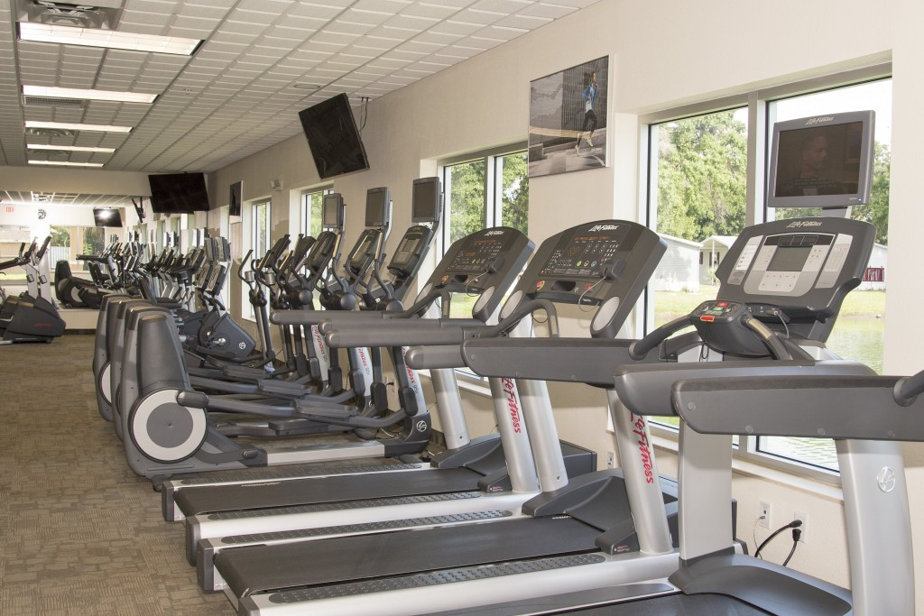Fully equipped fitness center with treadmills and stationary bikes. TVs are mounted to wall for enjoyment while working out.