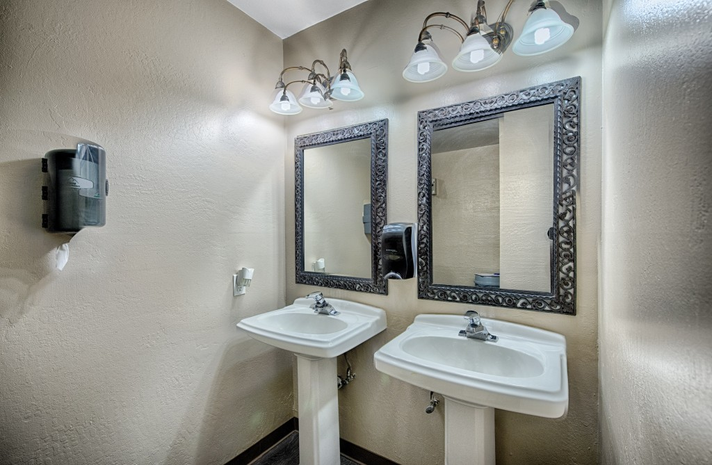 Bathrooms with sinks and mirrors inside locker room.