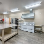 Remodeled clubhouse kitchen with hardwood floors, 2 stoves, microwave and large granite top island.