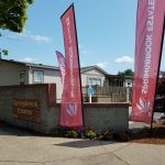 Entrance to Springbrook Estates with two burgundy flags stating Springbrook Estates positioned in the
