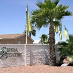 Sierra Estates entrance sign topped with blue and yellow flags