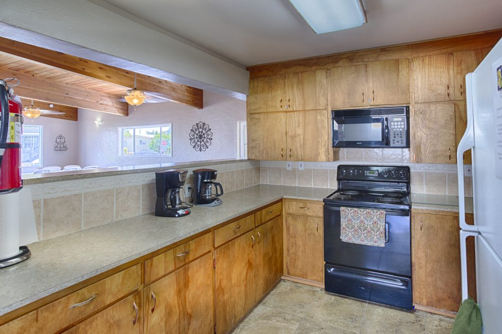 Community center kitchen connected to large, open hall. L shape counter top with ample space. Black appliances including a stove, oven, microwave and coffee makers. Wood cabinets throughout full size white fridge.