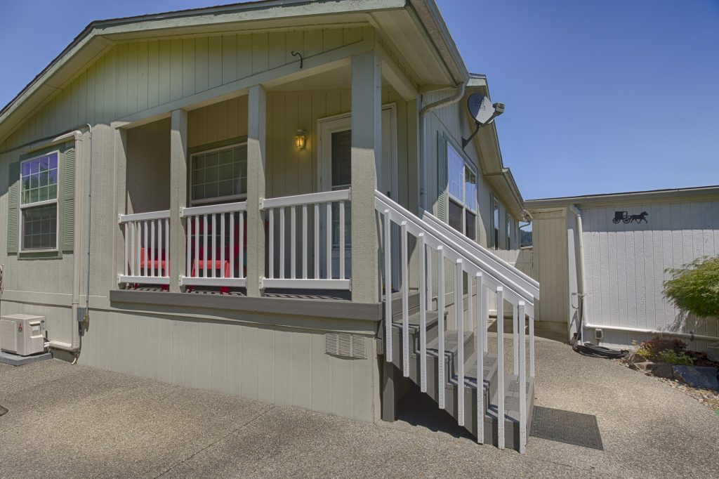 Beautiful manufactured home with a jade wood paneling exterior. Small staircase leads to covered front porch with white fencing and handles.