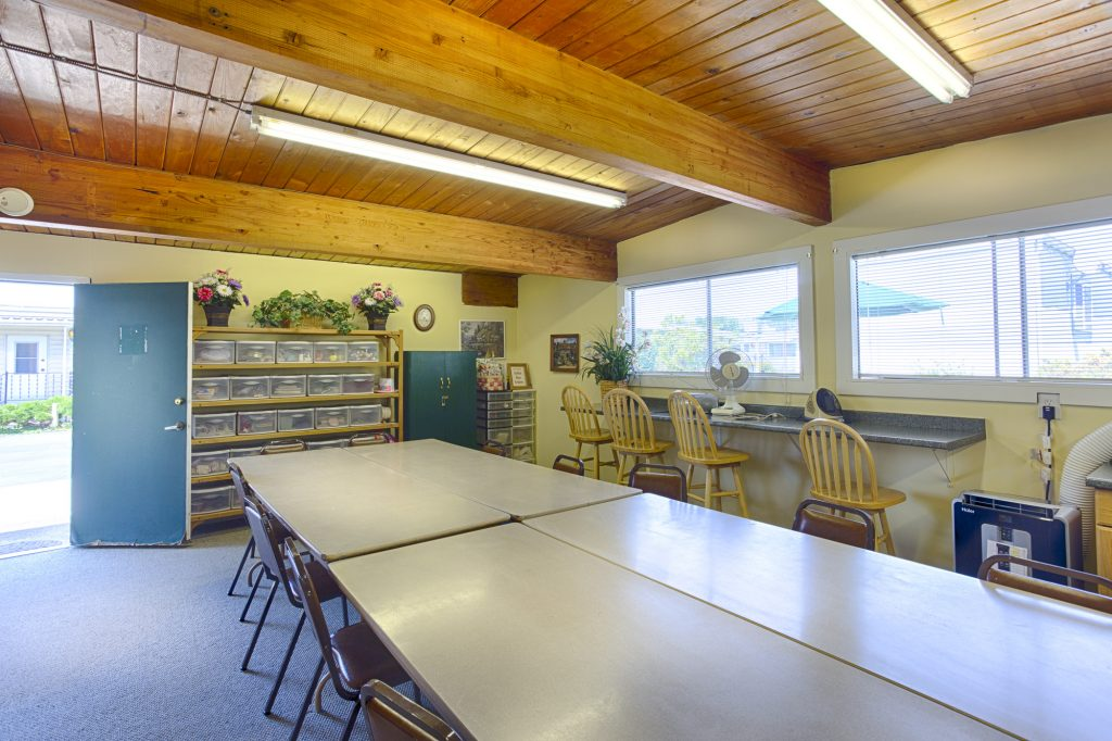 Arts and crafts center with connecting long tables and chairs. Available crafts along the walls within bins for residents to use. Ample seating for multiple users.
