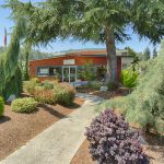 Community center surrounded by beautiful, well-maintained landscape of trees and plants. Rustic orange color of the center makes it pop within all the plant life.