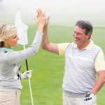 Well-dressed, and smiling man and woman high-fiving on the eighteen hole, green golf course.