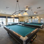 Quite large billiards room with five pool tables. Tvs mounted to wall. Plenty of lighting over each pool table.