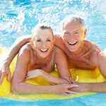 A mature, older couple enjoy their raft in the pool. The man and woman hold hands and smile.