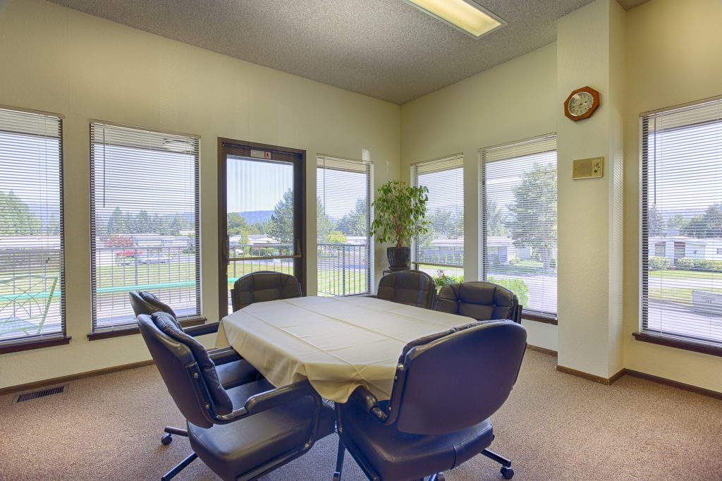 Oval table within the community center that fits six seats comfortably. Cushioned seats surround the table and have a beautiful view of the outdoors through the windows along the walls.