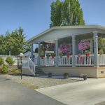 Beautiful manufactured home with large covered front porch. Colorful potted flowers hang around the perimeter of the porch.