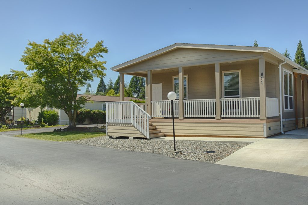 Beige colored manufactured home with small staircase leading up to long covered front porch. Very well-maintained front landscape for a clean look.