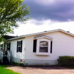 Manufactured home sits on large lot with lush green grass, tall trees and driveway to park car.