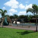 A big playground for children. There are monkey bars, slides, balance bar and swings. Bench seating is all around the perimeter of the playground.