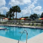 Gated swimming pool with lounge chairs, tables, and pool umbrellas. Lush green trees around community.