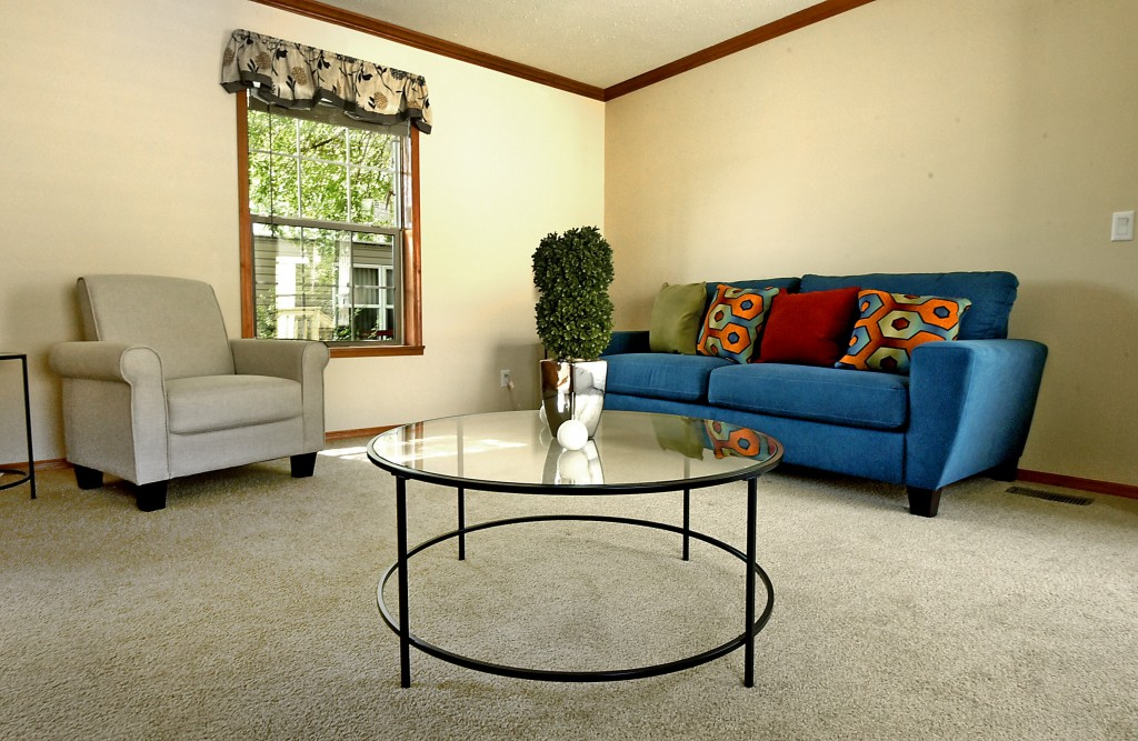 Our beautiful new manufactured homes have an open floor plan and spacious for a loveseat and ottoman. Round glass coffee table.