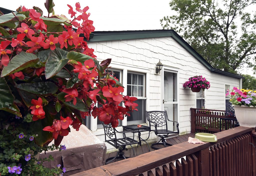 Rolling Hills Estates, an all age manufactured home community has homes with wood decks landscaped with colorful flowers of red and purple. Also a wrought iron patio set.