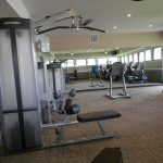 Remodeled gym with state of the art fitness equipment like weight machines and stationary bikes.