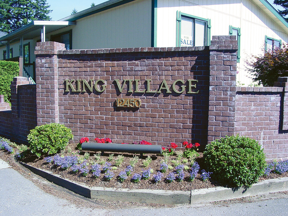 King Village sign on brick wall at entrance. Landscaped with small green shrubs and purple and red flowers.