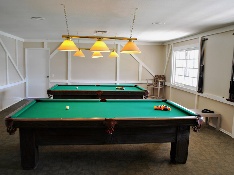 A billiard room with two pool tables.