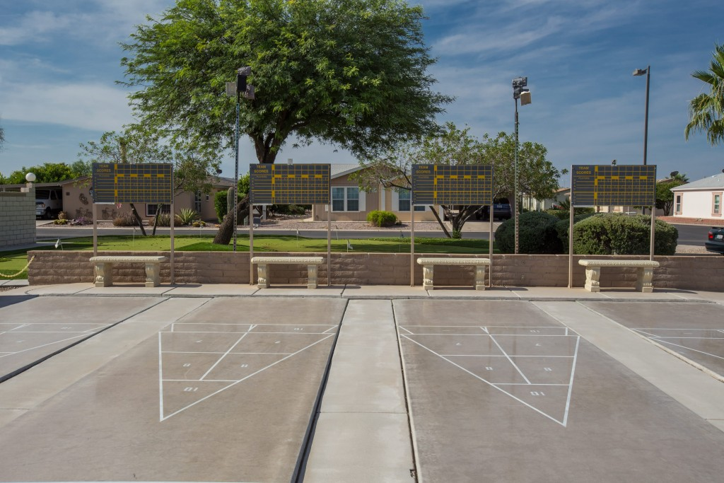 Four shuffleboard courts with scoreboards and seating