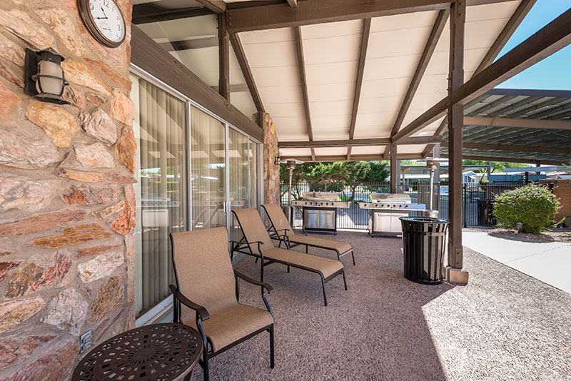 Relaxing outdoor shaded area outside of the community center. Access to two large gas barbeques, lounge chairs and a 3 piece seating set.