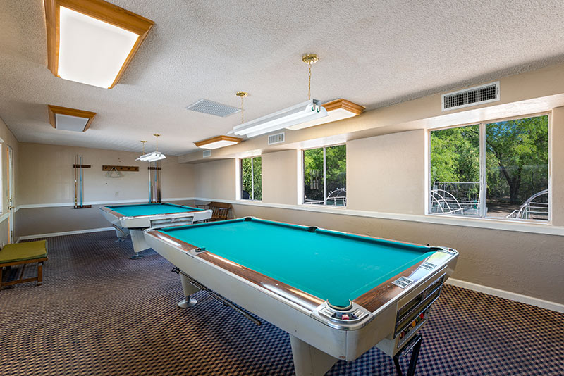 Billiards room with access to two billiards tables. Neutral colors throughout and windows with a view of the outdoors.