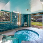 Beautiful indoor hot tub surrounded by blue tile walls and a light blue ceiling. Gold trimmings perimeter the windows and doors.