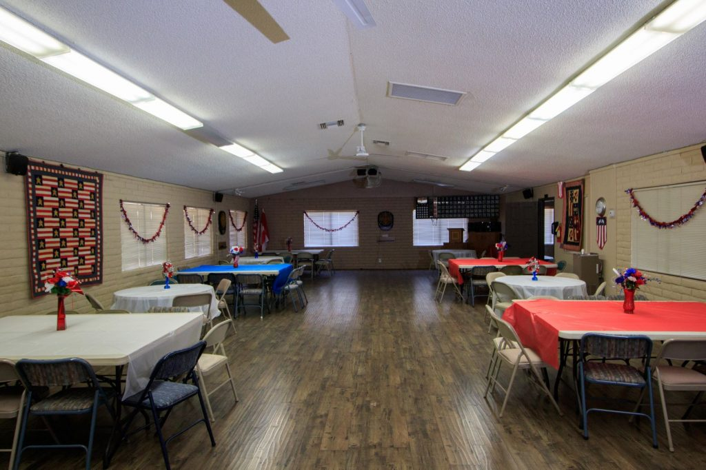 Large community room with multiple round and rectangular tables. and seating