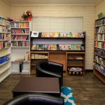 Small community library with walls that are filled with novels and comfortable seating.