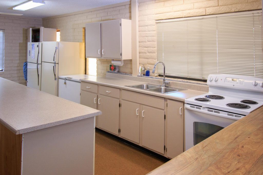 Large community kitchen located in the community hall. All white cabinets, counter tops,and appliances. Ample counter space and extra large island.