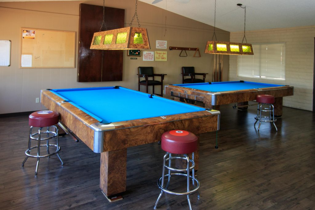 Billiards room. View of two of the tables with blue tops and eight-ball high stools. Hanging lights sit above eat table.