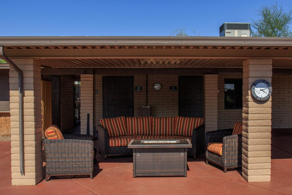 Comfortable outdoor seating with cushions situated under shaded area outside the clubhouse. One large couch and two single seats surround a small table.