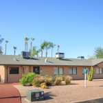 Leasing office of Pueblo Grande, a 55 plus community. Desert feeling with rocks and cactus in the foreground and terracotta coloring on the walkway.