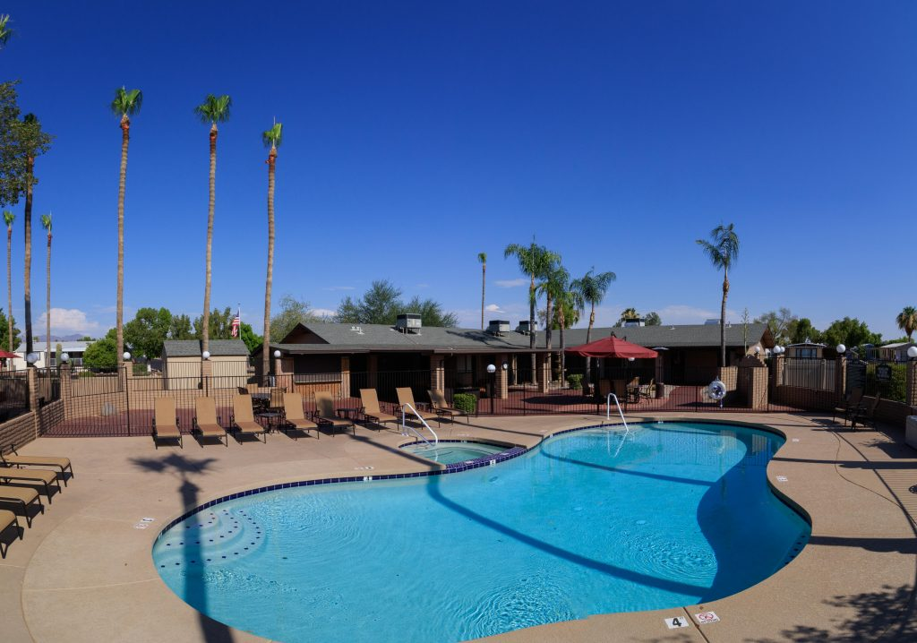 Beautiful poolside view with multiple chairs situated around for relaxation. Access to the community club house and outdoor dining area.