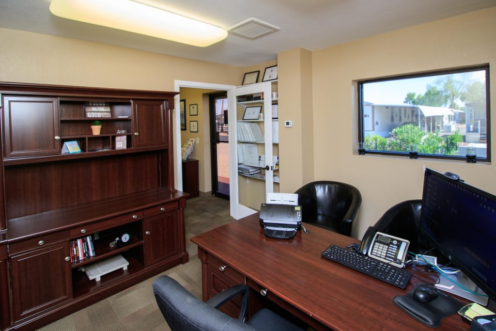 Interior of the leasing office. Open space with natural light and beautiful dark wood furniture and seating for potential residents