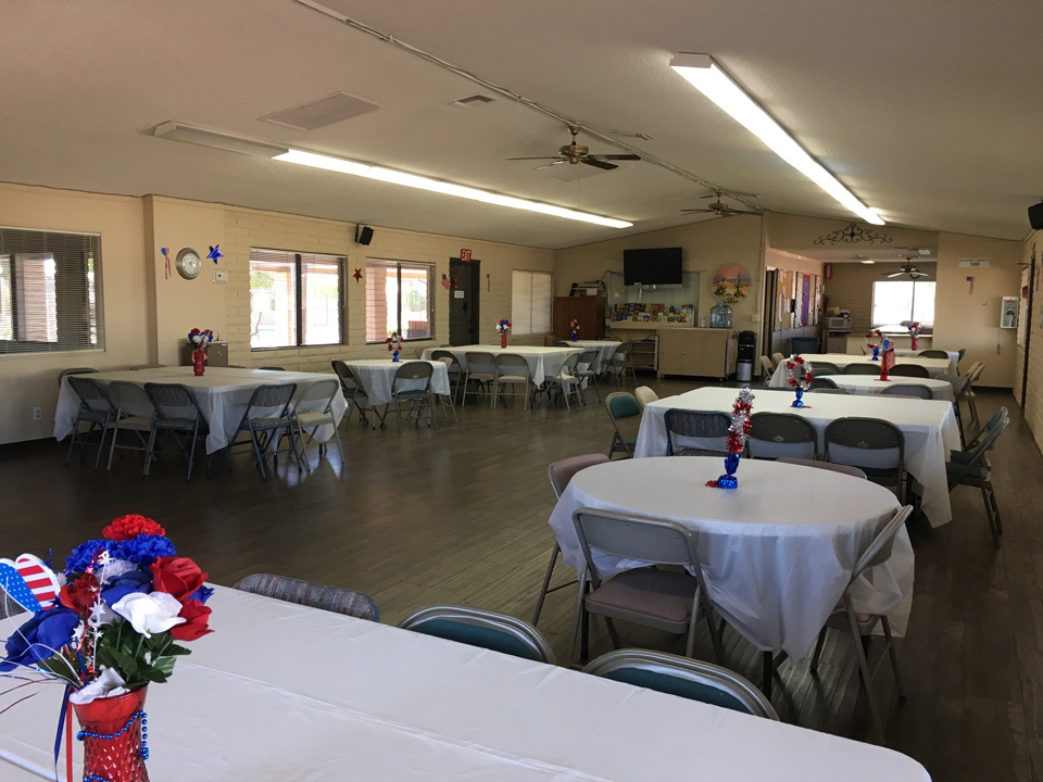 Large community room with covered banquet tables long and round and chairs. Red white blue flowers in a vase on them each.