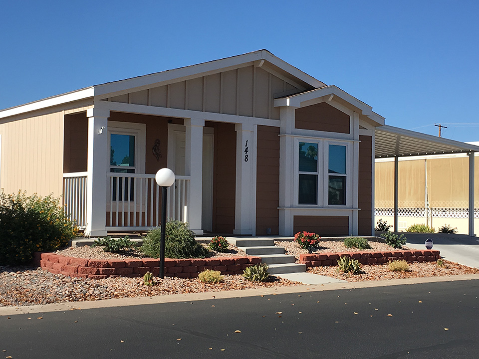 A brand new home. beige and white trim. Covered carport. Covered front porch with four small steps up to porch. Clean paved street.
