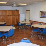 activity room with five round tables and four blue cheairs at each table