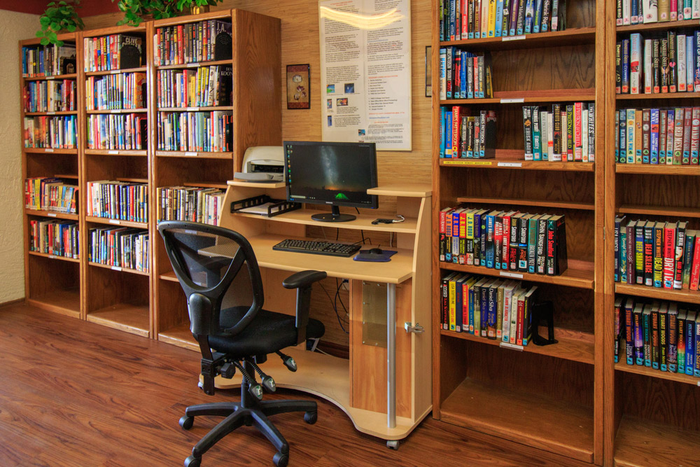 library with 3 book shelves filled with books and a small desk with office chair and community computer