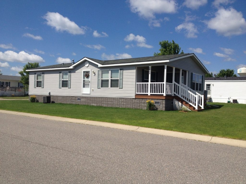 Avalon Estates, an all age manufactured home community offers homes with covered porches and green grass.
