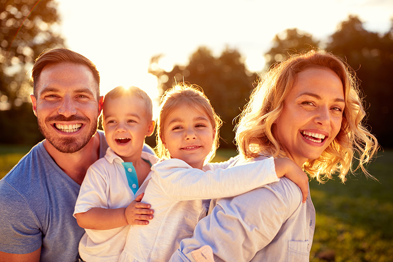 Camelot Estates, an all age manufactured home community, brings families together. A mother and father carry their son and daughter, smiling.